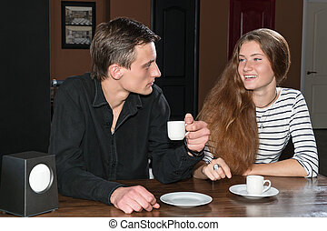 Man and woman having coffee in cafe - Man and woman sitting...