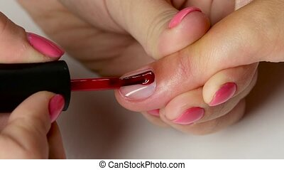 Master is stain the nail of client by red varnish. Close up...