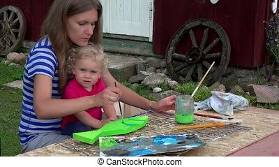 woman with little girl on knees paint wooden fish decoration in house yard