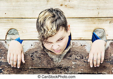 Young caucasian boy in medieval pillory. Negative emotions....