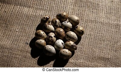 Quail eggs stacked on burlap. Rotating - Color of the shell...