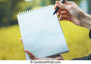 Woman writing in notepad outside - Woman's hands writing in...