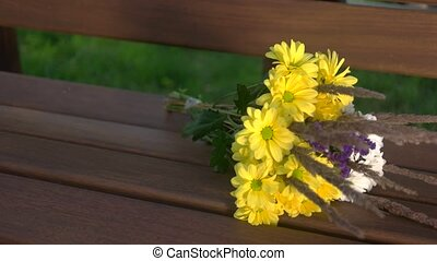 Bouquet on the bench. Yellow and white flowers. Camomiles...