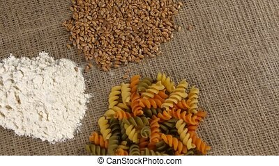 Heaps of pasta and flour and wheat. Close up. Rotating -...