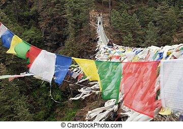 Rope hunging suspension bridge with row of prayer flags...