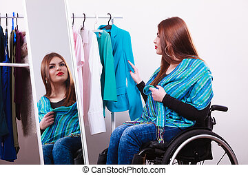 handicapped girl on wheelchair choosing clothes - Real...