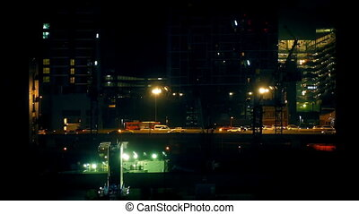 Road Between Buildings At Night - Vehicles passing in the...