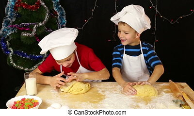 Two kids kneading the dough for christmas cookies together -...