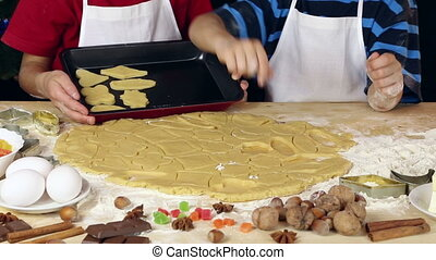 Two kids lay out the dough for xmas cookies to baking tray...