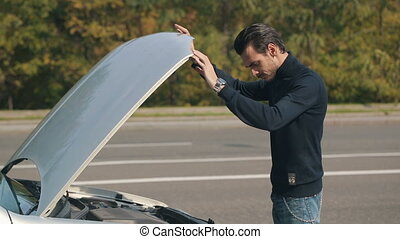 Man raises the car hood - Road trip car trouble. A young man...