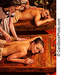 Couple in love having spa treatment on wooden bed. - Couple...