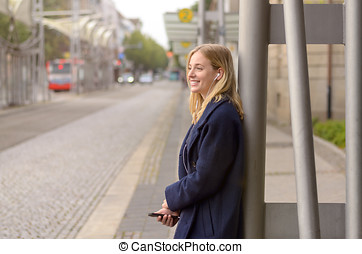 Smiling young woman waiting for her bus - Smiling young...