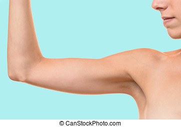 Young blond woman showing flabby arm, effect of aging caused...