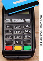 Payment terminal with contactless credit card on desk,...