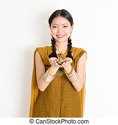 Celebrating Diwali festival - Mixed race Indian Chinese girl...