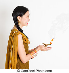 Woman holding Diwali diya light - Side view young mixed race...