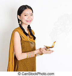 Woman holding diya light - Mixed race Indian Chinese girl in...