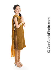 Woman in Punjabi costume greeting. - Young mixed race Indian...