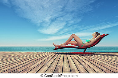 Young woman relaxing - Young woman in a bathing suit on a...