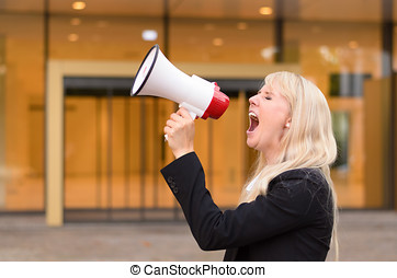 Angry woman protester yelling into a megaphone - Angry young...