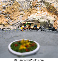 Miniature world: people waiting for their transport on the bus stop. Tourism and public transport theme.