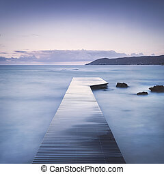 Wooden pier, rocks and sea on misty sunset. - Wooden pier or...