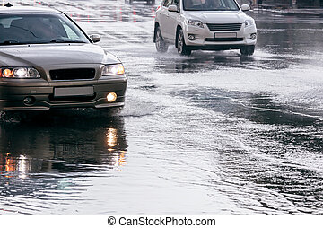 cars driving on water puddles after downpour - city road...