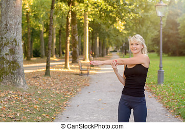 Smiling sporty young woman warming up - Smiling sporty young...