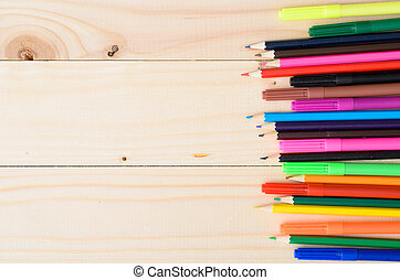 Colored pencils on a wooden board - Workplace. School or...