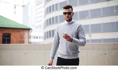 young man with sunglasses and bag walking in city -...