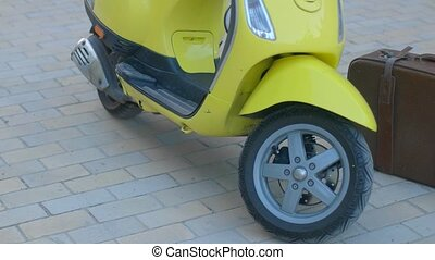 Yellow motor scooter. Dark brown suitcase. Things are...