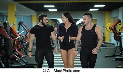 Group of talking people walk in fitness club - Girl and two...