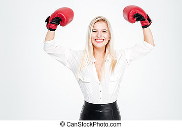 Cheerful young businesswoman in boxing gloves with raised...