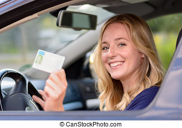 Happy young woman showing off her drivers license