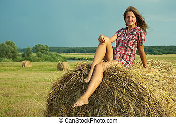 Country girl on fresh hay in summer