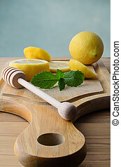 Sliced Lemons and Peppermint Leaves on Wooden Chopping Board