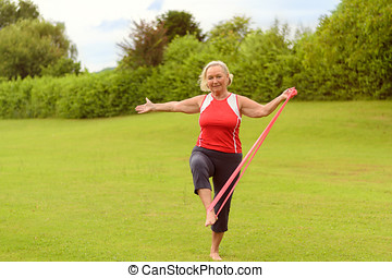 Fit senior woman using resistance bands with leg