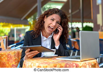 Frustrated businesswoman yelling into her mobile
