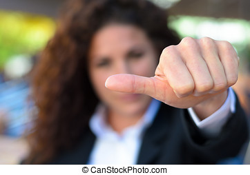 Woman abstaining from voting holding her thumb to the side...