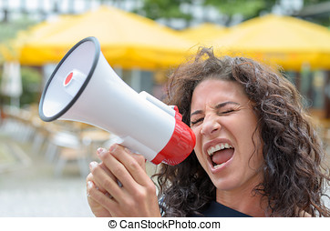 Attractive angry woman shouting into a megaphone outdoors n...
