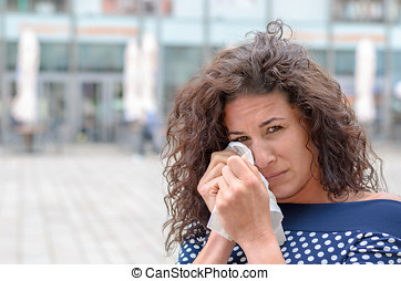 Tearful young woman wiping her eyes with a white...