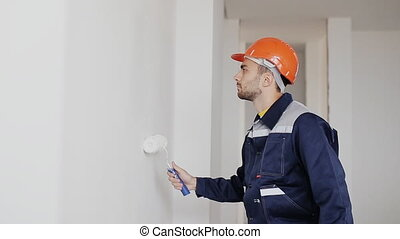 man decorating room. painting wall with paint roller -...
