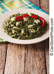 Indian Palak Paneer Spinach with cheese and spices close-up....
