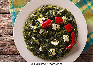 Palak paneer with spinach, cheese and hot peppers a closeup....