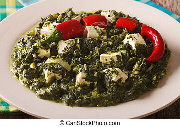 Indian Palak paneer in spicy spinach with cheese close-up....