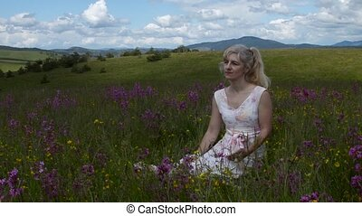 Woman Receiving Good News - Woman sitting in a meadow and...
