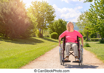 Elderly woman smiles while seated in wheel chair on a...