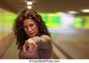 Stern young woman pointing at the camera with resolute...