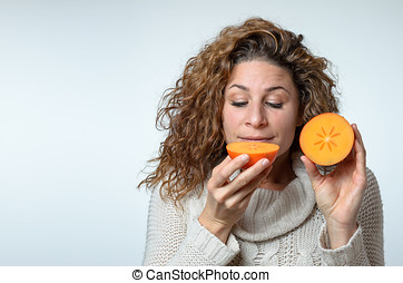 Healthy young woman enjoying a persimmon