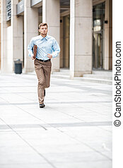 businessman with briefcase running - Young businessman with...